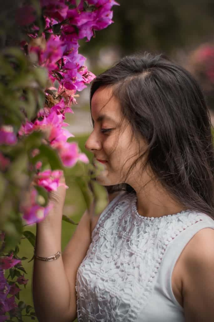 Brunette Girl Prioritising Self-Care Smiling And Smelling Pink Flowers